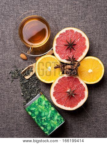 cup of green tea with fresh citrus fruits