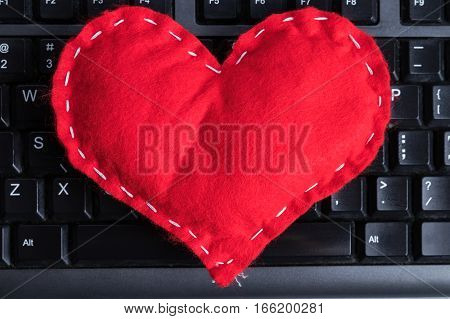 Red homemade heart on a computer keyboard on Valentine's Day.