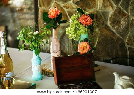 The vases with flowers on the white table