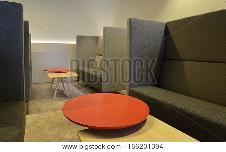 Interior corner for separated meetings, red table and grey sofa.