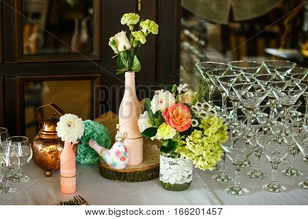 The wedding buffet table and vases with flowers
