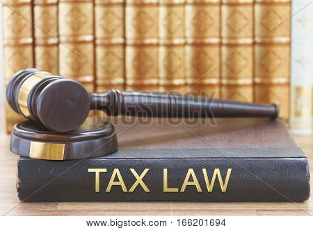 Wooden Law Gavel and a row of law books with tax law letters