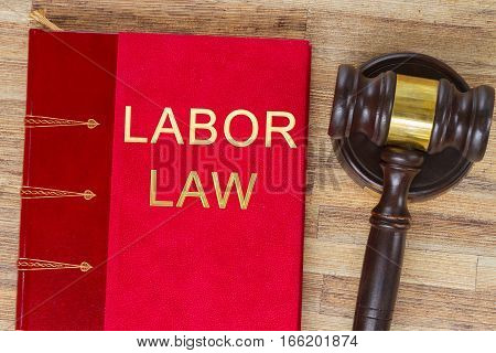 Wooden Law Gavel and legal labor law book on wooden desktop, top view poster