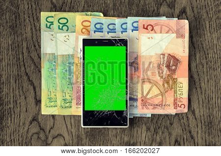 White Smartphone with broken screen on wooden table with money banknotes. Green chroma key display of damaged cellphone. Loss of connection concept