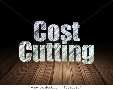 Business concept: Glowing text Cost Cutting in grunge dark room with Wooden Floor, black background
