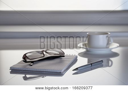 Table next to the window with a notebook and glasses in the office