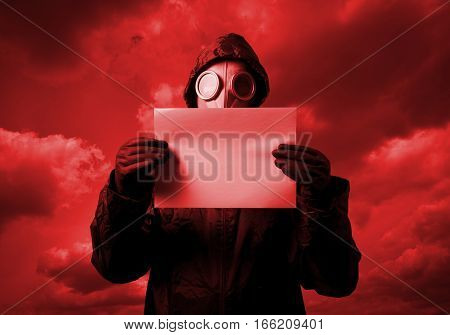 Man wearing a gas mask on his face and holding white paper. Red sky.