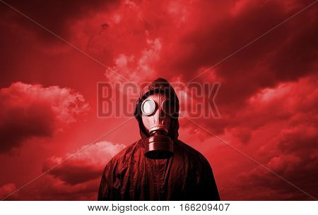 Man wearing a gas mask on his face. Gas mask and red sky.