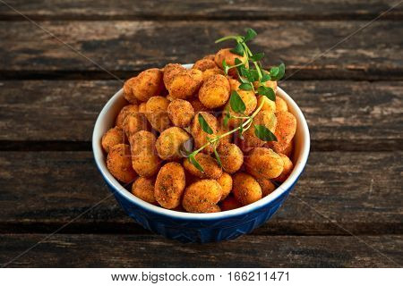 Crispy chilli peanuts snacks in blue bowl.