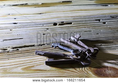 a bunch of rusty old keys on wooden background with a copy space