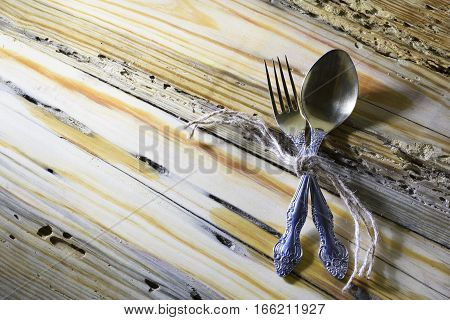 fork and spoon tied with a decorative rope on an old weathered wooden background with a copy space