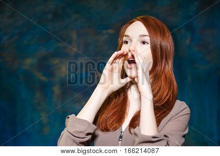 young emotional redhead girl shout with hands near mouth over blue background. Informing about