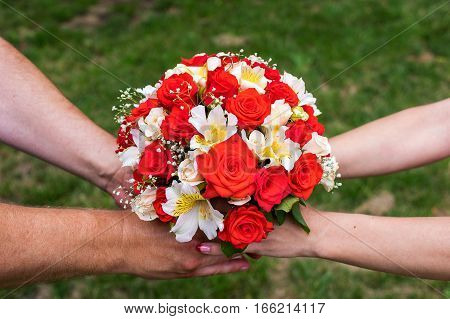 Close photo of the hands holding bouquet with wedding rings on it, symbolising marriage and unity.