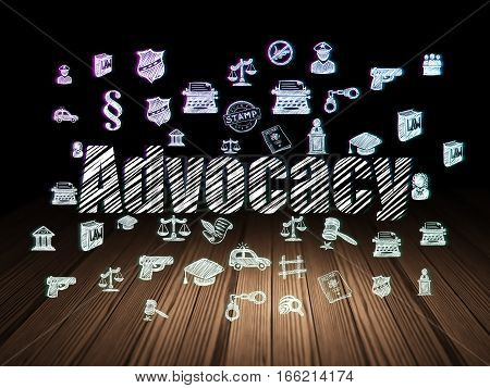 Law concept: Glowing text Advocacy,  Hand Drawn Law Icons in grunge dark room with Wooden Floor, black background