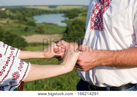 Close photo of man and woman hands holding together Couple in embroidered shirts are standing near the lake.