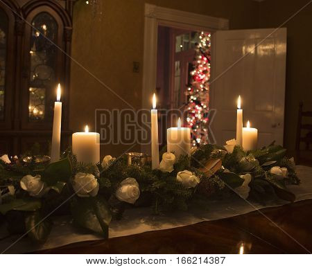 Candles in floral centerpiece on table at Christmas time with a tree in the background
