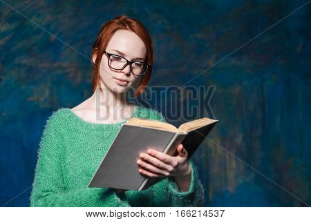 beautiful red-haired teacher in green sweater and glasses reading book over magic dark blue background