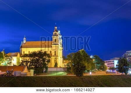 Night View Of Catholic Church Of St. Raphael The Archangel In Vilnius, Lithuania. Illuminated Street. Church Of The Late Baroque Built In The First Half Of The 18th Century.