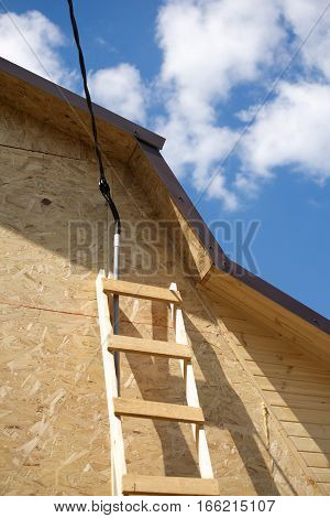 Power supply mounting on new built suburban house in summer day. Vertical photo