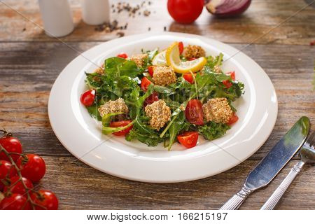fresh salad of cherry tomatoes, croutons and capelin roe, mixed lettuce leaves in a white dish on an old wooden table, top view