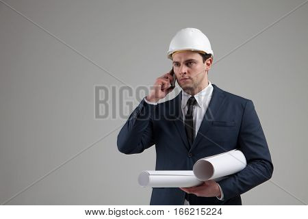 Portrait of a businessman in white helmet and in a stylish suit on gray background