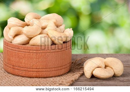 cashew nuts in a wooden bowl on the board with a blurred garden background.