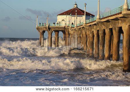 Manhattan Beach pier near Los Angeles, California with winter waves breaking.