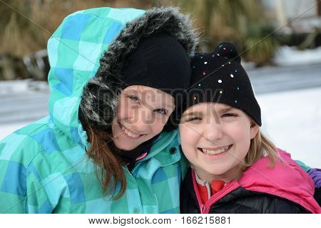 two girls happy outside in the snow