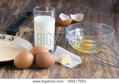 Fresh organic eggs milk and butter still life in rustic style on wooden background. Ready for cooking omlette.
