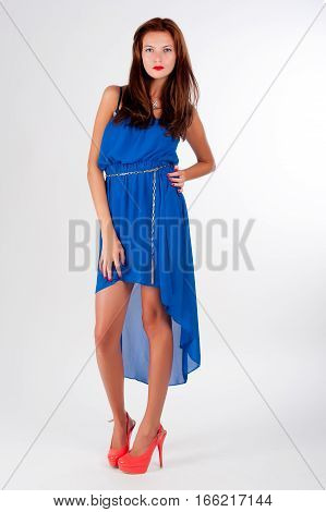 Attractive red-haired girl with freckles wearing beautiful dress and high heels shoes. Studio shot over white background