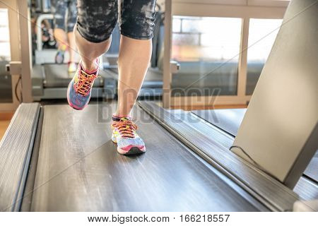 Close up of woman legs in colorful shoes running on treadmill machine in gym. Fast training indoor. Healthy active lifestyle concept.