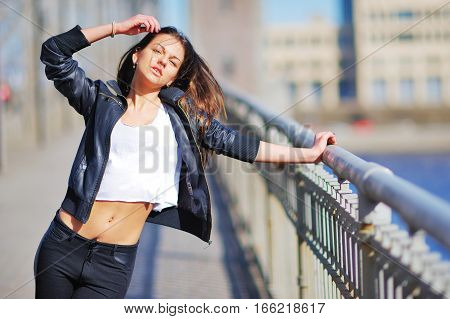 Portrait of slim sexy woman of bridge wearing a short white t-shirt above navel black leather jacket and pants at hips. She straightens her disheveled hair eyes narrowed from bright sun.