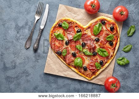 Heart shaped pizza delicious love concept Valentine's Day flat lay romantic restaurant dinner Italian food. Olives, prosciutto, basil, tomatoes and mozzarella meal on blue table background.