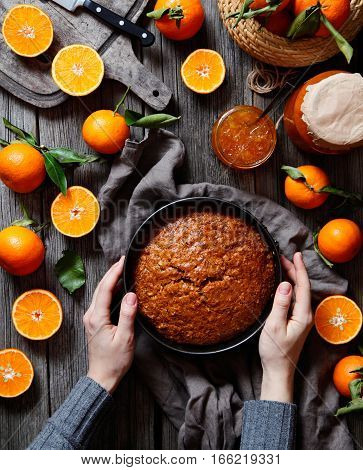 Tangerines compositions. Homemade Citrus Tangerine cake, orange pie or tart, biscuit of citrus on a dark wooden background with hands in the frame decorated with tangerines. View from above.