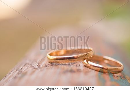 Close up photo of the wedding rings lying on the wooden bench. Macro shot with narrow field of view
