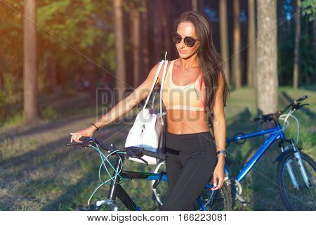 Fit woman with bike standing in park