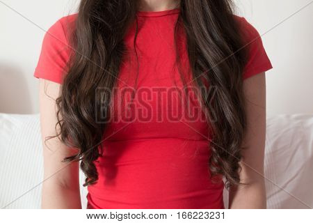 Part of young woman with long hair in red shirt