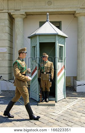 Budapest Hungary - 05 July 2015 : Guards of President's Sandor Palace. One of the guards deliver to others driking water during the summer heat.