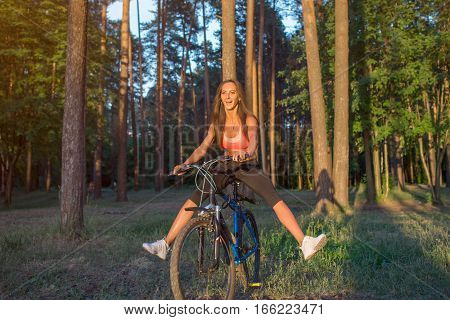 Woman riding bicycle with stretching her legs in the air