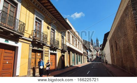 Quito, Pichincha / Ecuador - January 22 2016: Couple walking in the Historic Center of Quito with the Basilica of the National Vow in background