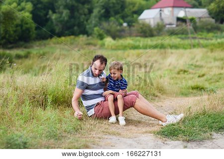Father and son spending time together. Dad playing with his child at nature. Happy family spending time together outside at meadow.