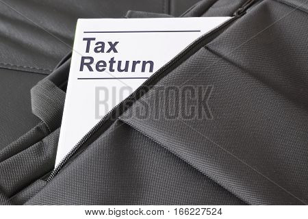 Open briefcase with some documents in it. A paper with the title TAX RETURN written on it. Empty copy space for Editor's text.