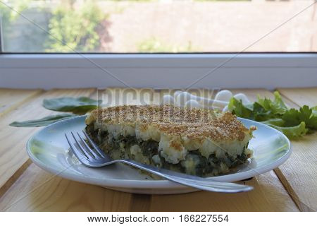 Portion of casserole with potatoes and spinach on a wooden table near the window.