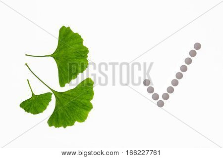gingko leaves with tick mark made of pills on white background