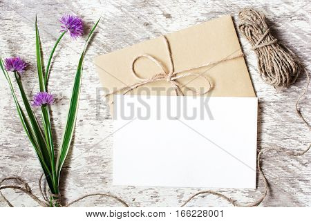 Blank white greeting card and envelope with purple wildflowers on white rustic wood background for creative work design. flat lay