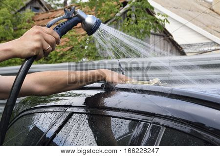 outdoor car wash using water hoses. Close up