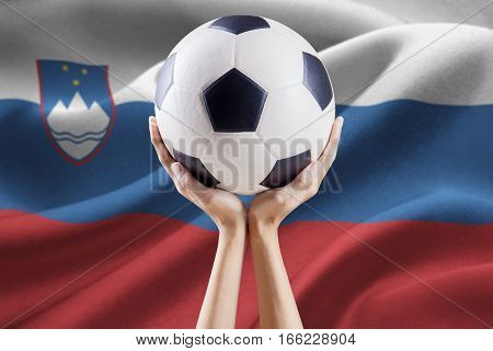 Image of two arms holding a soccer ball with national flag background of Slovenia