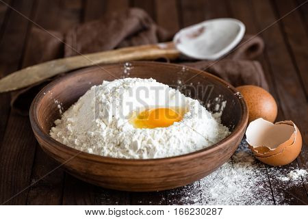 flour and egg on wooden background close up