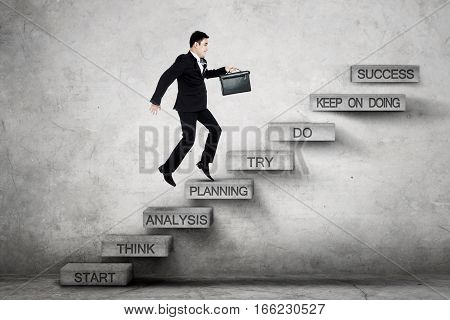Picture of businessman stepping on the stairs with planning text toward success while carrying a briefcase