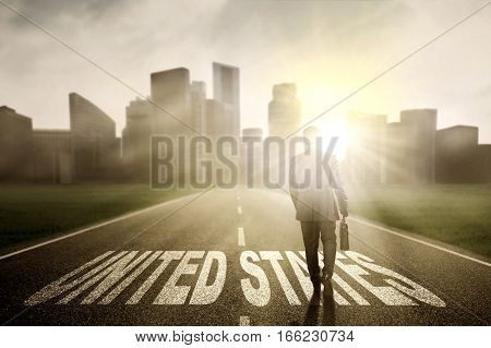 Back view of businessman walking on the street while carrying a briefcase with United States word at sunrise